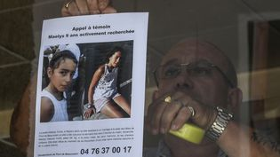 Un homme placarde un appel à témoins, le 28 août 2017, àPont-de-Beauvoisin (Isère), après la disparition de Maëlys. (PHILIPPE DESMAZES / AFP)