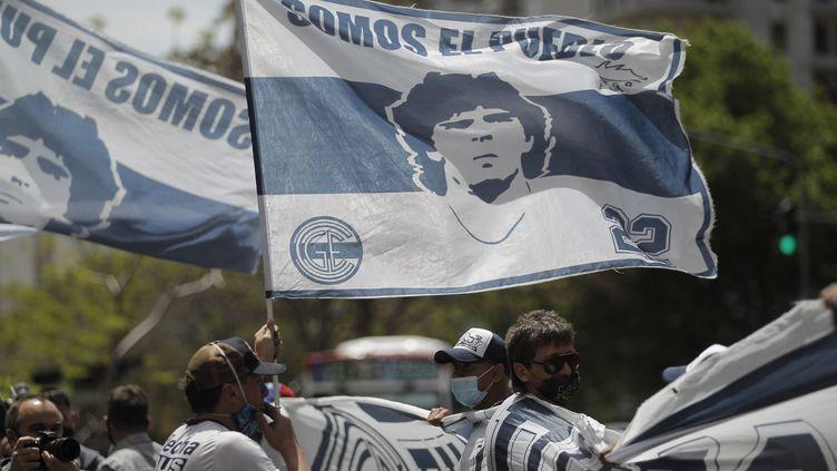 Des fans de Diego Maradona brandissent des drapeaux à son effigie, devant une clinique de La Plata (Argentine) où était hospitalisé l'ancien footballeur, le 4 novembre 2020. (EMILIANO LASALVIA / AFP)