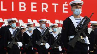 Les membres de l'École des mousses de la Marine nationale portentdes masques de protections lors du défilé du 14 juillet. (LUDOVIC MARIN / AFP)