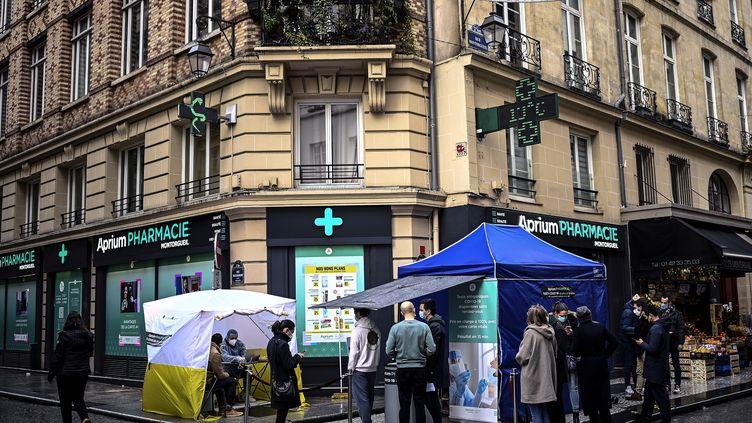 Des patients font la queue devant une pharmacie pour réaliser un test antigénique de dépistage du Covid-19, à Paris, fin décembre 2020. (CHRISTOPHE ARCHAMBAULT / AFP)