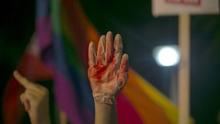 Un manifestant brandit un gant ensanglanté lors d'un rassemblement contre les violences homophobesà Tel Aviv (Israël), le 1er août, deux jours après une attaque contre la Gay Pride de Jérusalem. (BAZ RATNER / REUTERS)