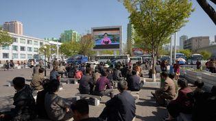 Des habitants de Pyongyang regardent la télévision d'Etat lorsque Kim Jong-un annonce qu'il entend cesser ses tests de tirs de missiles et son programme nucléaire, le 21 avril 2018. (KIM WON-JIN / AFP)