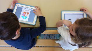 Des élèves de maternelle produisent un livre numérique sur les tablettes prêtées par l'Education nationale, à Puligny-Montrachet (Côte-d'Or), le 14 avril 2015. (CAMILLE CALDINI /FRANCETV INFO)