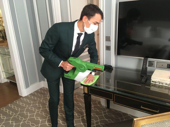 Alexandre Germain, directeur de l'entretien au Crillon, utilise son pistolet électrostatique pour nettoyer une chambre du palace, début septembre 2020. (GREGOIRE LECALOT / RADIO FRANCE)