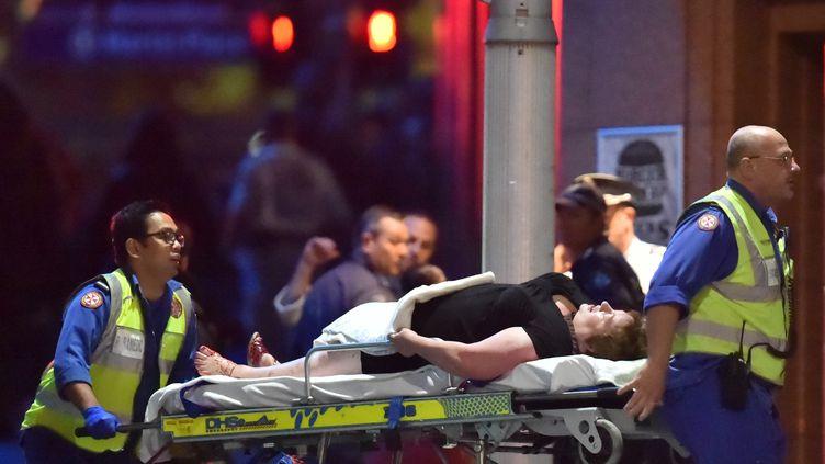 Un otage blessé est transporté par les secours, mardi 16 décembre 2014 à Sydney (Australie). (PETER PARKS / AFP)