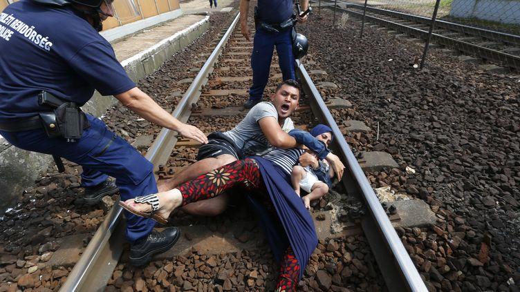Les policiers hongrois tentent de dégager unefamille des migrants des rails, à la gare deBicske (Hongrie), le 3 septembre 2015. (LASZLO BALOGH / REUTERS )
