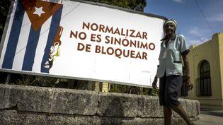 Un homme passe devant une affiche dénonçant le blocus américain, le 26 octobre 2016, à La Havane (Cuba). (ADALBERTO ROQUE / AFP)