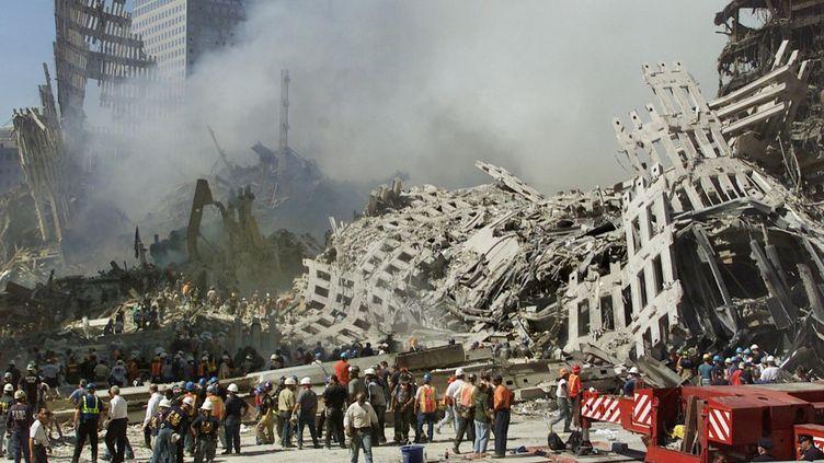 Les secouristes poursuivent leurs recherches alors que de la fumée s'élève des décombres du World Trade Center, le 13 septembre 2001 à New York.  (BETH A. KEISER / AP POOL)