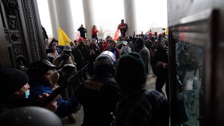 La police intervient pour évacuer des partisans de Donald Trump qui ont fait irruption au Capitole, à Washington (Etats-Unis), le 6 janvier 2021. (MOSTAFA BASSIM / ANADOLU AGENCY / AFP)