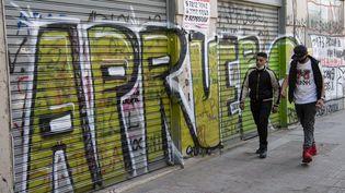 Desjeunes chiliens passent devant un graffiti en référence au référendum du 25 octobre visant à modifier la constitution du pays, à Santiago le 21 octobre 2020. Photo d'illustration. (MARTIN BERNETTI / AFP)