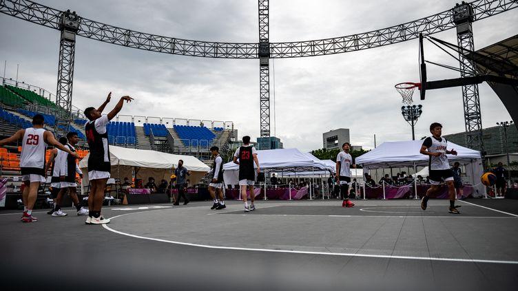 Des joueursjaponais s'échauffent avant un match de basket 3x3, à Tokyo le 16 mai 2021. (PHILIP FONG / AFP)