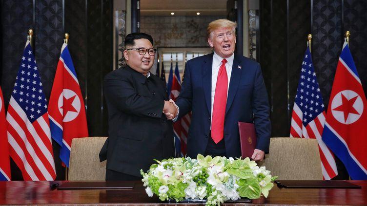 Kim Jong-un et Donald Trump se serrent la main, le 12 juin 2018, à Singapour, avant la signature d'un document commun. (KEVIN LIM / THE STRAITS TIMES / ANADOLU AGENCY / AFP)