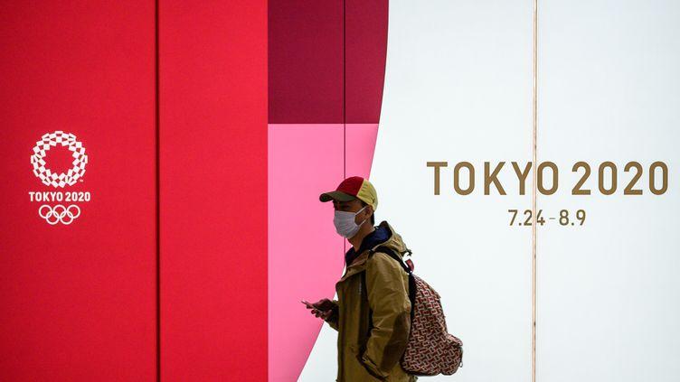 Un homme devant le logo des JO à Tokyo en mars 2020. (PHILIP FONG / AFP)