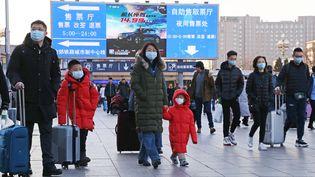 Des passants portent des masques dans une gare de Pékin, le 20 janvier 2020,en raison de l'épidémie decoronavirus. (KOKI KATAOKA / AFP)