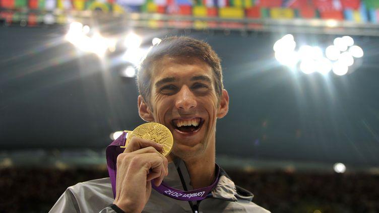 Michael Phelps avec sa médaille d'or sur 100m papillon à Londres en 2012. (CHRISTOPHE SIMON / AFP)