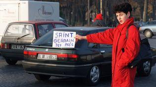 A la surface, la circulation n'est pas plus aisée. Cette jeune femme fait ainsi du stop pour tenter de rejoindre le quartier de Saint-Germain-des-Prés, le 30 novembre 1995. (MICHEL GANGNE / AFP)