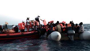 Des membres de l'association SOS Méditerannée viennent en aide à des migrants dans la zone de recherche et de secours de la mer du même nom, le 9 juin 2018. (KARPOV / SOS MEDITERRANEE)
