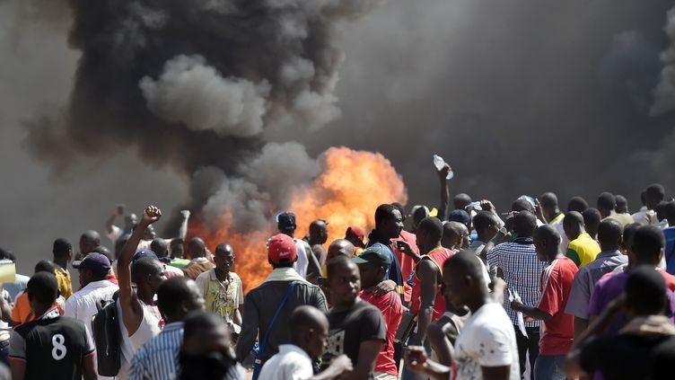 Des Burkinabés manifestent devant l'Assemblée, le 30 octobre 2014 à Ouagadougou (Burkina Faso),contre un projet de révision constitutionnelle qui permettrait au président de se représenter. (ISSOUF SANOGO / AFP)