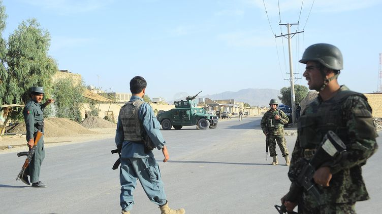 Soldats et policiers afghans patrouillent près de la base américaine de Kandahar (Afghanistan), le 27 octobre 2011. (JANGIR / AFP)