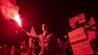 Un manifestant tenant un fumigène lors d'une manifestation pour le droit à l'avortement, à Varsovie (Pologne), le 30 octobre 2020. (WOJTEK RADWANSKI / AFP)