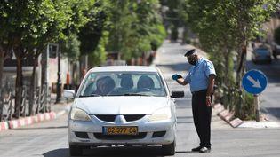Un policier palestinien contrôle un véhicule, le 3 juillet 2020, en pleine crise sanitaire du coronavirus. (ISSAM RIMAWI / ANADOLU AGENCY)