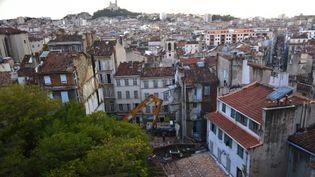Une grue évacue, le 6 novembre 2018, les décombres de deux immeubles qui se sont effondrés la veille dans la rue d'Aubagne, dans le centre de Marseille. (EMIN AKYEL / AFP)