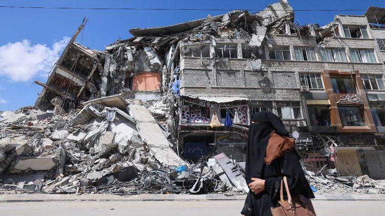 Une femme palestinienne devant un bâtiment détruit, le 22 mai 2021 à Gaza. (EMMANUEL DUNAND / AFP)