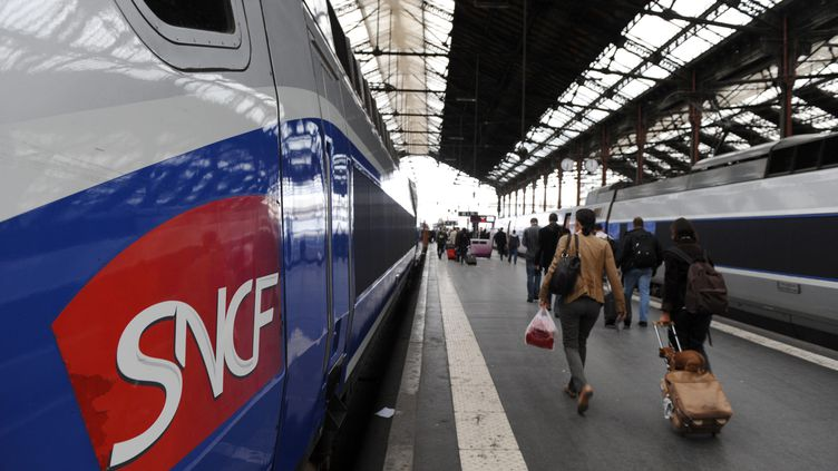 Des usagers de la SNCF marchent sur le quai à côté de TGV avant le départ de leur train le 6 octobre 2011 en gare de Lyon à Paris. (MIGUEL MEDINA / AFP)