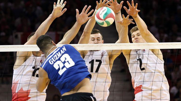 Des volleyeurs canadiens contrent un ballon envoyé par leur adversaire portoricain durant un match le 26 juillet 2015. (Kevin Hoffman / REUTERS)