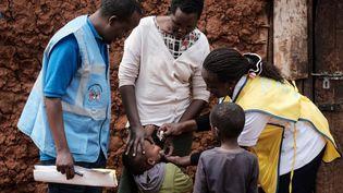 Un garçon reçoit des gouttes de vaccin contre la polioadministré parune infirmière à domicile, à Kajiado, au Kenya, le 11 juillet 2018. L'aide au développement a permis l'éradication de cette maladie sur le continent africain. (YASUYOSHI CHIBA / AFP)