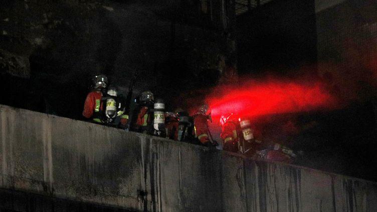 Des pompierssur un balcon après avoir maîtrisé l'incendie d'un immeuble d'habitationdu 19e arrondissement boulevard Macdonald à Paris, le 6 avril 2019. (GEOFFROY VAN DER HASSELT / AFP)