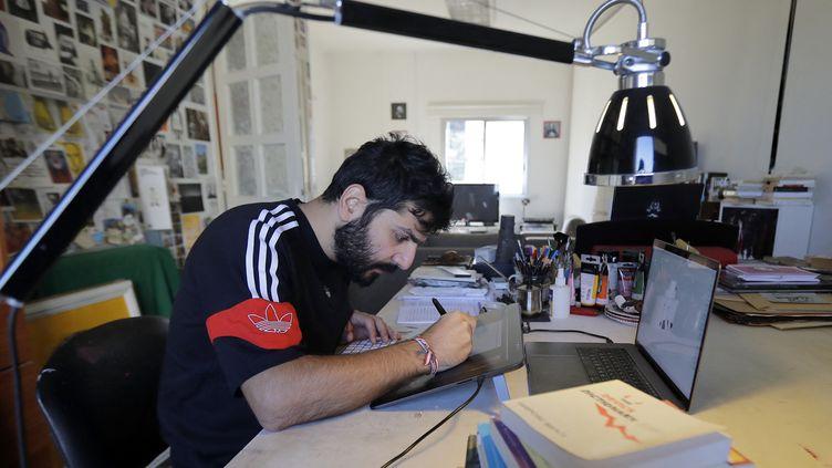 Le caricaturiste libanais Bernard Hage travaille dans son studio à Jal el-Dib, dans la banlieue nord de la capitale Beyrouth. (JOSEPH EID / AFP)
