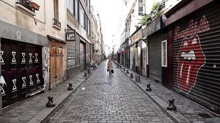 Une femme passe devant des commerces fermés de la rue de Lappe à Paris. (STEFANO RELLANDINI / AFP)