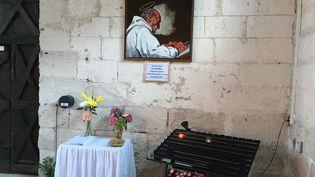 Un tableau représentant le père Jacques Hamel a été accroché au mur de l'glise de Saint-Etienne-du-Rouvray (Seine-Maritime), le 19 juillet 2017. (RAPHAEL GODET / FRANCEINFO)