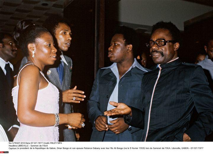 Le président du Gabon Omar Bongo (à droite) et son épouse Patience Dabany, accompagnés de leur fils Ali Bongo (au centre), lors du sommet de l'Organisation de l'unité africaine (OUA) à Libreville, au Gabon, le 7 juillet 1977. (FRILET/SIPA)