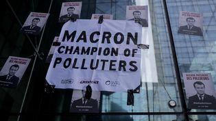 """Des affiches collées par desmilitants écologistes à La Défense, le 19 avril 2019, dans le cadre d'une action de """"désobéissance civile"""" pour le climat. (THOMAS SAMSON / AFP)"""