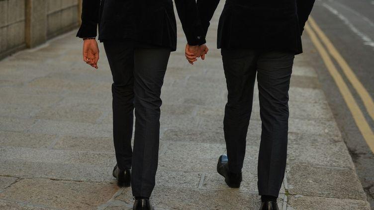 Deux hommes se tiennent la main dans les rues de Dublin (Irlande), le 27 novembre 2020. (ARTUR WIDAK / NURPHOTO / AFP)