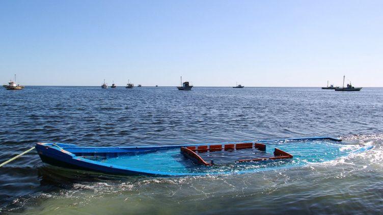 Unbateau, qui transportait 29 personnes et qui a coulé au large des côtes tunisiennes, en train d'être remorqué près de la ville côtière tunisienne d'Amra, le 13 octobre 2020. (HOUSSEM ZOUARI / AFP)