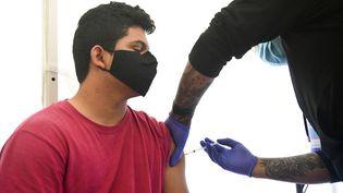 Un adolescent reçoit une dose du vaccin de Pfizer/BioNTech, le 23 avril 2021 à Los Angeles (Etats-Unis). (FREDERIC J. BROWN / AFP)