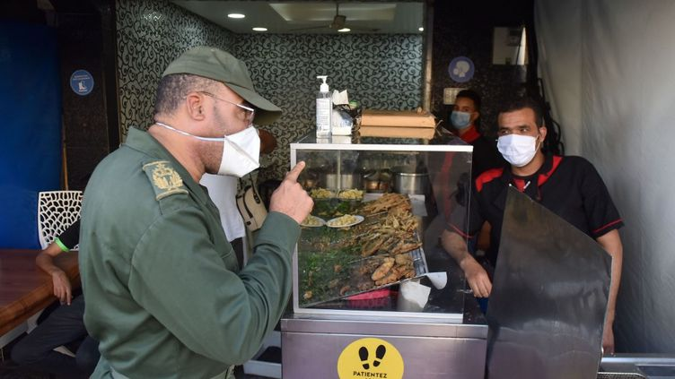 Les forces de sécurité demandent aux habitantsde se conformer aux mesuressanitaires pour endiguer la propagation du coronavirus à Salé, au Maroc, le 27 décembre 2020. (JALAL MORCHIDI / ANADOLU AGENCY)