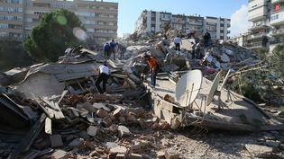 Des personnes recherchent des rescapés dans unimmeuble effondré à Izmir, en Turquie, le 30 octobre 2020. (MEHMET EMIN MENGUARSLAN / ANADOLU AGENCY / AFP)