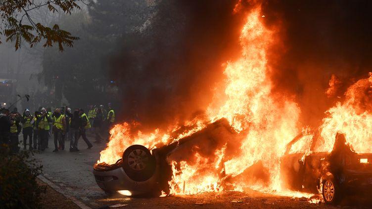 Des véhicules incendiés dans une rue de Paris le 1er décembre 2018. (ALAIN JOCARD / AFP)