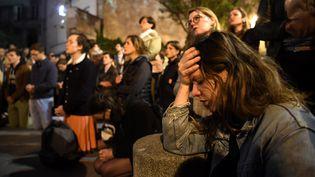 A 20h, ils sont déjà des dizaines à se rassembler sur la place Saint-Michel, au plus près de la cathédrale, pour voir ce qu'il se passe et se recueillir. Des chants chrétiens résonnent. Les riverains ont eux été évacués, par mesure de sécurité. (ERIC FEFERBERG / AFP)