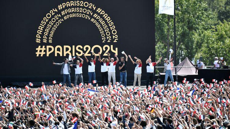Le 8 août 2021 à Paris, des athlètes participent à la cérémonie de transmission de la flamme olympique entre Tokyo et la capitale française. (STEPHANE DE SAKUTIN / AFP)
