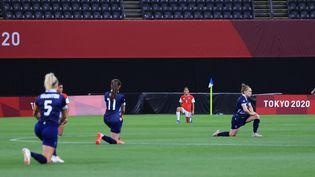 Les footballeuses britanniques (en bleu) et chiliennes (en rouge) s'agenouillent avant le début de leur match à Sapporo, le 21 juillet 2021. (TAKUYA MATSUMOTO / YOMIURI / AFP)
