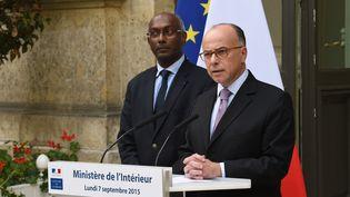 Le ministre de l'Intérieur, Bernard Cazeneuve (à droite), a nomméKléber Arhoul (à gauche) coordinateur national pour l'accueil des migrants dans les villes volontaires. (LOIC VENANCE / AFP)