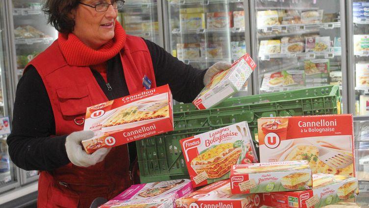 Une employée d'un supermarché de Wittelsheim(Haut-Rhin) retire des rayons les plats surgelés à base de viande,après le scandale sur la viande de cheval, le 11 février 2013. (MAXPPP)