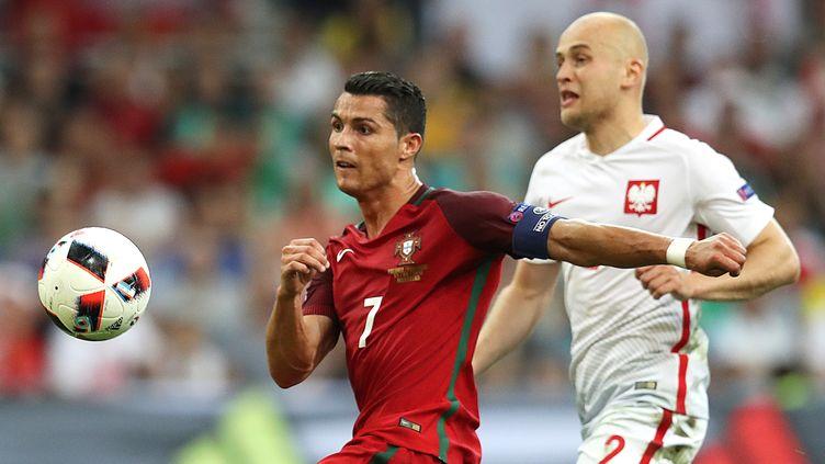 Le Portugais Cristiano Ronaldo à la lutte avec le Polonais Michal Pazdan, le 30 juin 2016 au stade Vélodrome de Marseille. (VALERY HACHE / AFP)