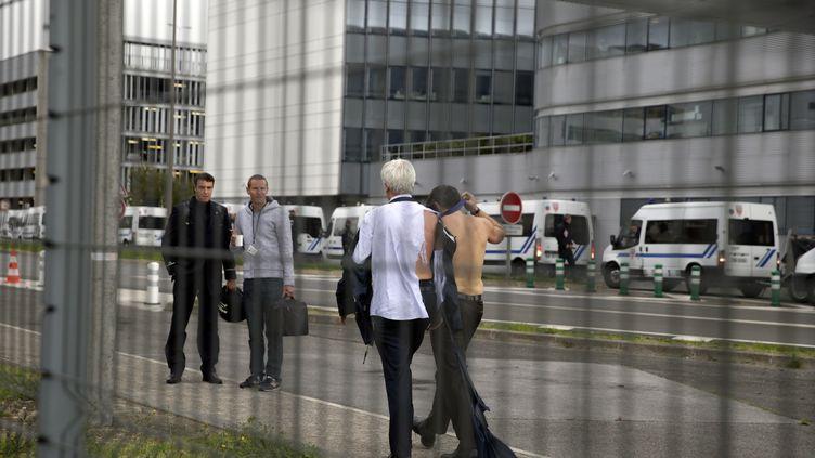 Le directeur des ressources humaines des vols long-courriers d'Air France, Pierre Plissonnier (à g.), et le vice-président exécutif d'Air France Ressources humaines et Relations de travail, Xavier Broseta, torse nu, s'éloignent des manifestants, accompagnés de policiers anti-émeute, le 5 octobre 2015. (KENZO TRIBOUILLARD / AFP)