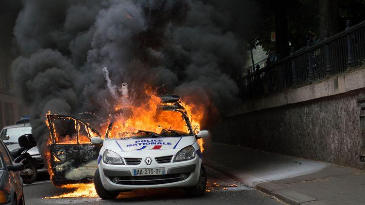 Une voiture de police incendiée par des manifestants, quai de Valmy, à Paris, le 18 mai 2016. (CYRIELLE SICARD / AFP)